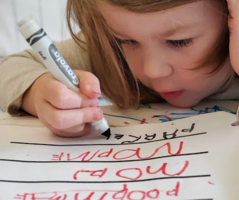 little girl practicing to write
