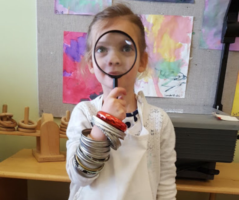 little girl with a magnifying in her face